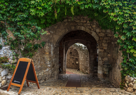 Old ivy covered archway in the picturesque medieval city of Eze Village in the South of France along the Mediterranean Sea