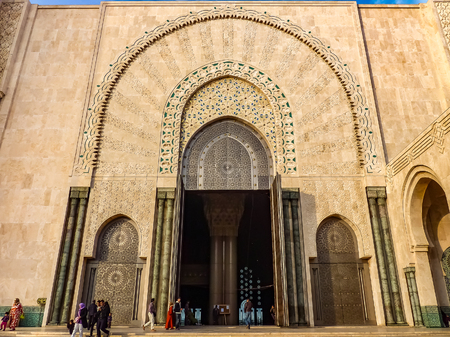 Casablanca, Morocco - December 9, 2012: People walking near the ornate gates of the Mosque Hassan II