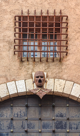 Iron Mask above an old gate in Le Suquet on the Tour du Masque, a tower that is haunted by the ghost of the man in the Iron Mask near the castle of Castre in Cannes, France Standard-Bild - 111846280