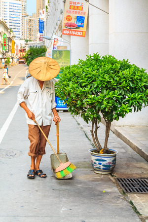 September 14, 2013 - Xiamen, China: Street sweeper sweeps a busy shopping street in center of the city