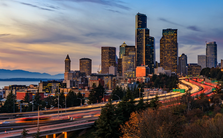 Seattle downtown skyline and skyscrapers  beyond the I-5 I-90 freeway interchange at sunset with long exposure traffic trail lights from Dr. Jose Rizal or 12th Avenue South Bridge