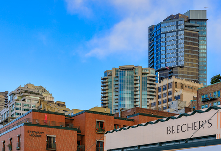 Seattle, United States - November 08, 2018: Famous Beechers Cheese store sign and Seattle terraced waterfront skyline by the Pike Place Market Editorial