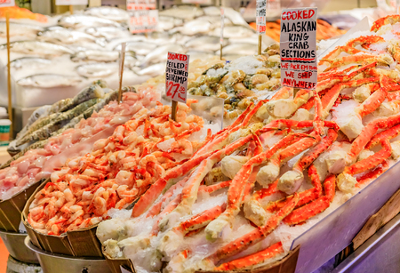 Fishmonger at a stall with fresh seafood like crab and shrimp for sale at Pike Place Market in Seattle, Washington Stock Photo