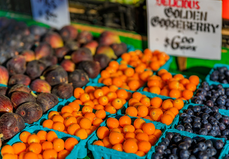 Assortment of fresh fruits like gooseberry, figs and blueberries for sale at a stall at Pike Place Market in Seattle, Washington
