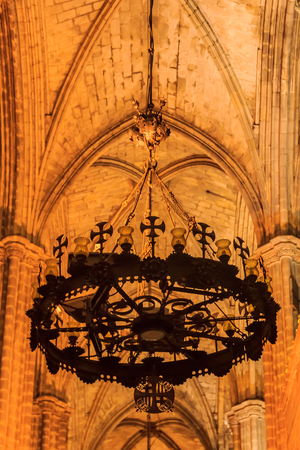 Ornate metal chandelier in a dark gothic cloister of the Cathedral of the Holy Cross and Saint Eulalia, or Barcelona Cathedral in Barcelona, Spain Stock Photo