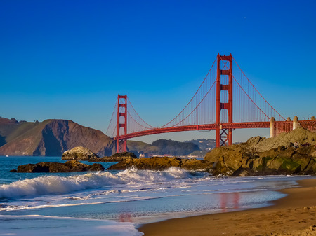 Waves rolling in a the Golden Gate Bridge on Baker Beach just before sunset