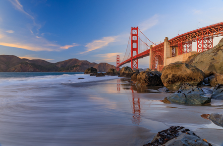 Famous Golden Gate Bridge view from the hidden and secluded rocky Marshall's Beach at sunset in San Francisco, California Фото со стока - 114910822
