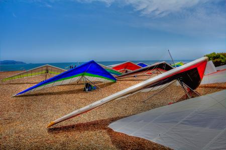 Farbenfrohe Drachenflügel, die auf einer Klippe in Fort Funston in San Francisco aufgereiht sind, einem der besten Drachenflugplätze des Landes