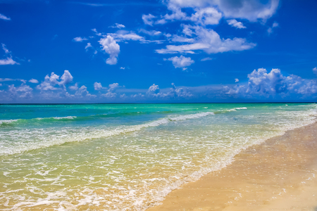 The turquoise water of the Caribbean sea on a tropical sandy beach with beautiful clouds in the sky in Freeport, Bahamas