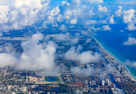 Aerial view of turquoise waters of the Atlantic Ocean along the eastern coast of Florida in Miami with Miami Golden Beach and Holliwood Beach coastline viewed through cloud cover Archivio Fotografico - 114913772