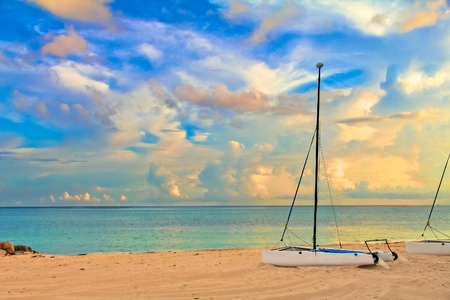 Catamaran on a tropical beach by the turquoise waters of the Caribbean sea, Freeport, Bahamas and stunning clouds in the background at sunset