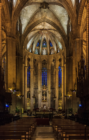 Dark gothic nave and the altar with with ornate arches in the Cathedral of the Holy Cross and Saint Eulalia, or Barcelona Cathedral in Barcelona, Spain
