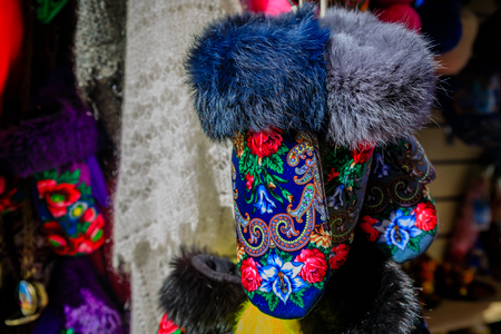 Warm fur trimmed winter gloves with traditional Russian design patters for sale at an open air market in Saint Petersburg, Russia with warm shawls in the background