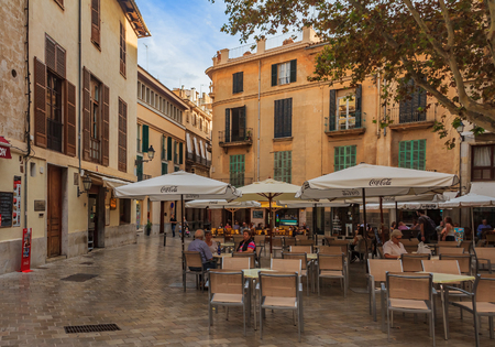 Palma de Mallorca, Spain - October 22, 2013: Small square with an open air street café and old buildings in the background in the old town