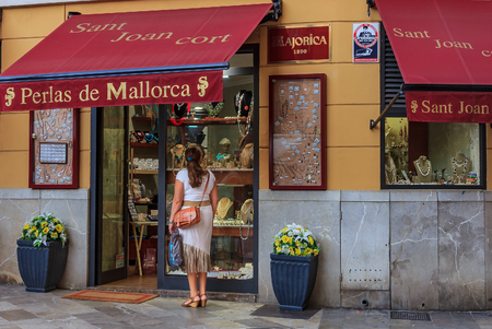 A young women looking at pearl jewelry on display in a jewelery shop in Palma de Mallorca in Mallorca in Spain, Maillorca is famous for pearls 新聞圖片