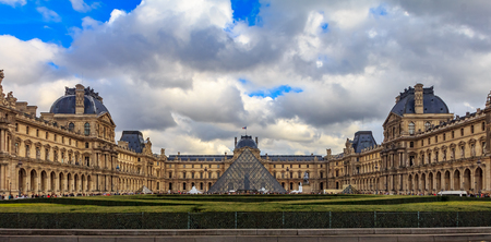 Paris, France - October 25, 2013: Panoramic view of the facade of the famous Louvre Museum, one of the worlds largest art museums and a historic monument with the Pyramid in front