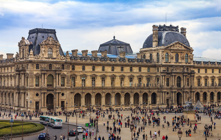 Paris, France - October 25, 2013: Tourists walking in front of the famous Louvre Museum, one of the worlds largest art museums and a historic monument 新聞圖片