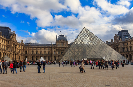 Paris, France - October 25, 2013: Tourists walking in front of the famous the Pyramid and the Louvre Museum, one of the worlds largest art museums and a historic monument with