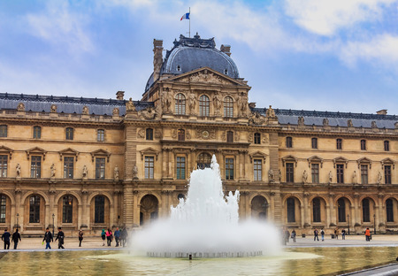 Paris, France - October 25, 2013: Facade of the famous Louvre Museum, one of the worlds largest art museums and a historic monument with a fountain in front