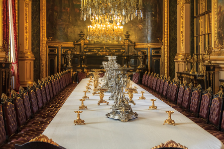 Paris, France - October 25, 2013: Banquet table in the apartments of Napoleon III in Louvre Museum with luxury baroque furnishings and stunning chandeliers
