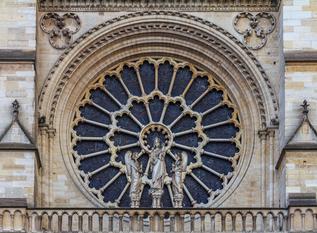 Closeup view of the Notre Dame de Paris Cathedral facade with the oldest rose window installed in 1225 which forms a halo above the Virgin with Child statue placed in front of it