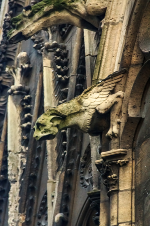 Gothic gargoyles covered in moss on the facade of the famous Notre Dame de Paris Cathedral in Paris France