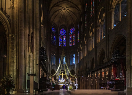 View onto the pulpit, the altar and the cross of the Notre Dame de Paris Cathedral with the stained glass windows along the back wall during a mass in Paris France