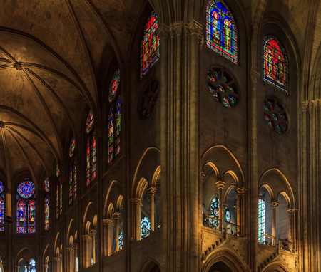 Closeup of stained glass windows along the side wall, arched cloister and ceiling in the Notre Dame de Paris Cathedral in Paris France
