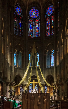 View onto the altar and the cross of the Notre Dame de Paris Cathedral with the stained glass windows along the back wall in during a mass Paris France
