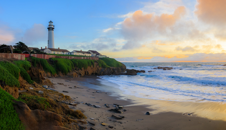 Panorama with pastel colors of sunset and silky water from long exposure of waves crashing on the shore by Pigeon Pight Lightouse on Northern California Pacific Ocean coastline near Pescadero