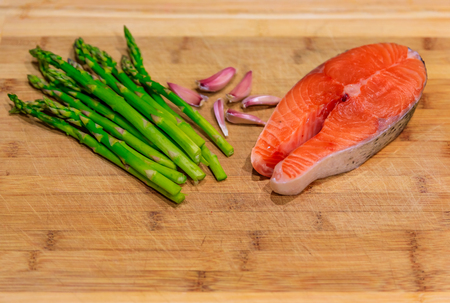 Fresh salmon steak surrounded with garlic and asparagus on a wooden cutting board Stock Photo
