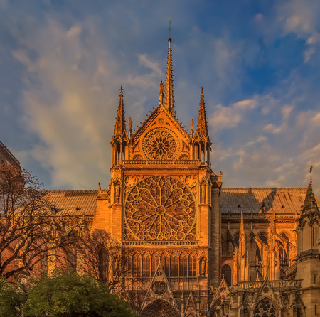 Details of the southern facade of Notre Dame de Paris Cathedral facade with the rose window and ornate spires colored by the warm light of sunset