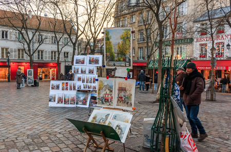 Artists awaiting customers amongst easels and artwork set up in Place du Tertre in Montmartre Paris, France 報道画像