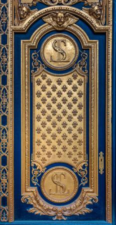 Ornate golden door with fleur de lis pattern at the entrance of Les Invalides in Paris France burial site of Napoleon Bonaparte