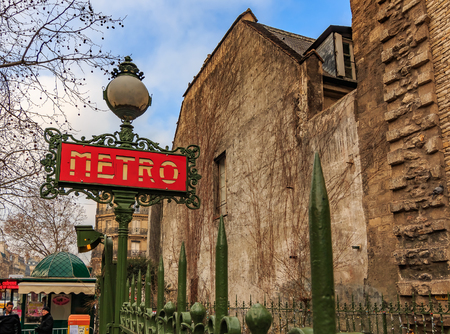 Ornate red art deco or art nouveau Parisian metro sign near by the Saint Germain des Pres church and Merto stop in Paris France 新聞圖片
