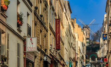 View along the street onto to old restaurant with windmill Moulin de la Galette in the Montmartre district in Paris, France