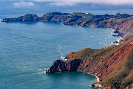 Rugged coastal cliffs above the Pacific Ocean by the Point Bonita Lighthouse in Marin County California, flying from San Francisco, USA