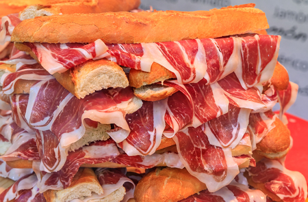Stack of serrano iberico ham sandwiches on display at a local sandwich shop in Madrid, Spain