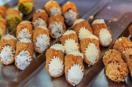 Freshly made traditional Italian cannoli with a variety of fillings on display at a bakery in Ventimiglia, Italy
