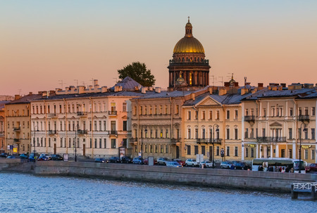 Sunset in Saint Petersburg, Russia over the Neva river with the view of the Palace Embankment and the Saint Isaacs Cathedral