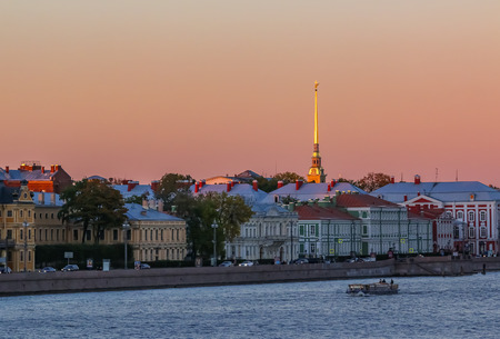 Sunset in Saint Petersburg over the Neva river with the view of the Palace Embankment and the spire of the  Fortress tower