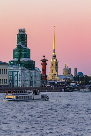 Sunset in Saint Petersburg over the Neva river with the view of the Palace Embankment, the Rostral column and the spire of the  Fortress tower