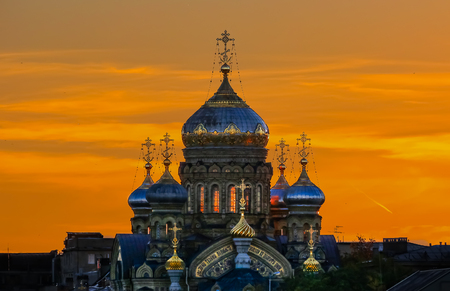 Ornate golden domes and crosses of the Russian Orthodox Church of the Assumption of Mary on the river Neva in Saint Petersburg Russia in a fiery sunset 版權商用圖片