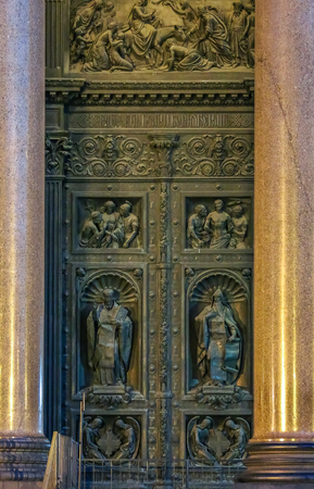 Close up of sculptures of saints on the relief on the doors of Saint Isaacs Russian Orthodox Cathedral in Saint Petersburg, Russia at sunset