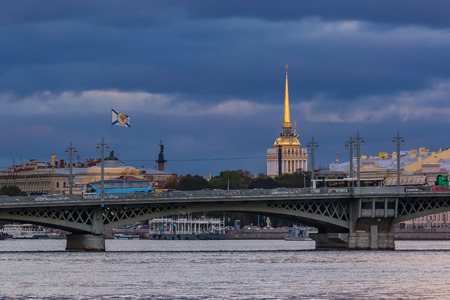 Sunset in Saint Petersburg over the Neva river with the view of Blagoveshchenskiy Bridge and the spire of the Admiralty or Admiralteystvo tower