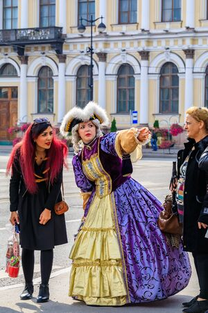 Saint Petersburg, Russia - September 10, 2017: Female entertainer dressed in period dress approaching tourists for photo opportunities near Palace Square