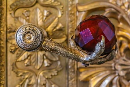 Saint Petersburg, Russia - October 4, 2015: Ornate door handle with a stylized eagle foot and a red crystal in the Hermitage museum in the Winter Palace