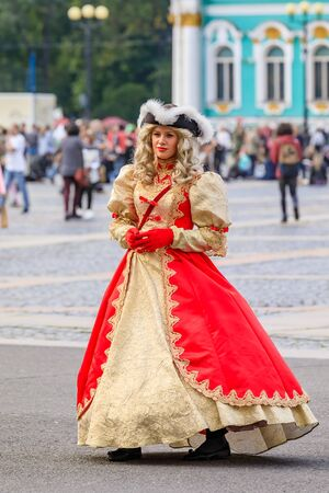 Saint Petersburg, Russia - September 10, 2017: Female entertainer dressed in period dress awaiting tourists for photo opportunities in front of the Winter Palace - Hermitage on Palace Square