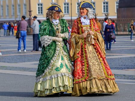 Saint Petersburg, Russia - September 10, 2017: Female entertainers dressed in period dresses awaiting tourists for photo opportunities in front of the Winter Palace - Hermitage on Palace Square Editorial