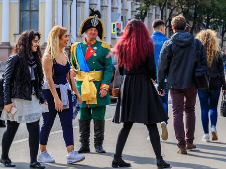 Saint Petersburg, Russia - September 10, 2017: Male entertainer dressed in period outfit approaching tourists for photo opportunities near Palace Square